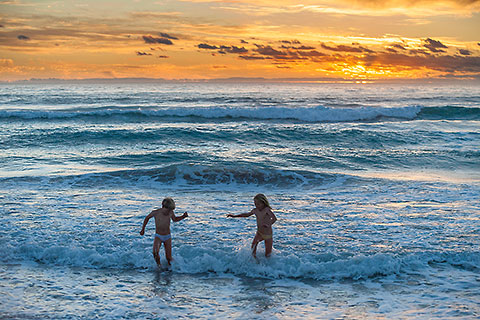 Enya & James playing in waves at sunset [©2010 paulgodard.com]
