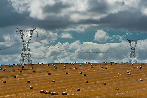 clouds & electrical pilones over wheat field with hay rolls [©2014 paulgodard.com]
