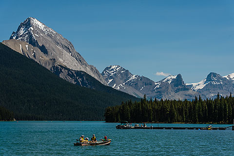 boat on Maligne lake with pine tree forest & Leah/Samson peaks of Maligne mountains  [©2017 paulgodard.com]