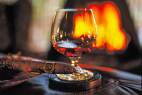 glass of cognac & Cuban cigar on leather table in front of fire [©2000 paulgodard.com]